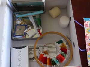 Inside my embroidery box: a small metal box with finger protectors, punch needle, ripper, scissors, marker, and plastic bobbins. two round sponges (to use as pin cushions for now), wooden ring, and that Avon box holds my needles.