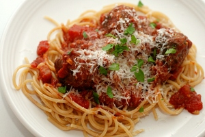 Spaghetti topped with cheese and meatballs in tomato sauce. Courtesy www.crumblecookie.com